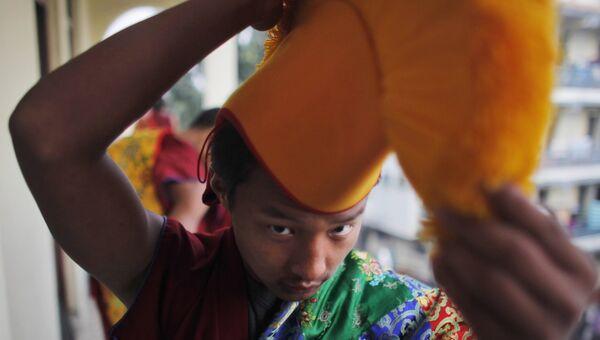 Монах надевает головной убор перед торжественной церемонией в честь 25-летия вручения Нобелевской премии мира Далай-ламе. 10 декабря 2014