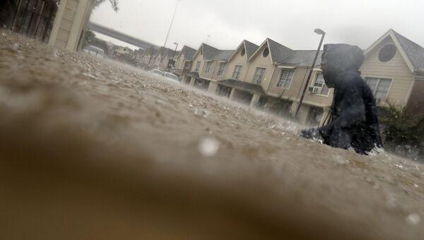 Подросток пробирается сквозь затопленные тропическим штормом Харви