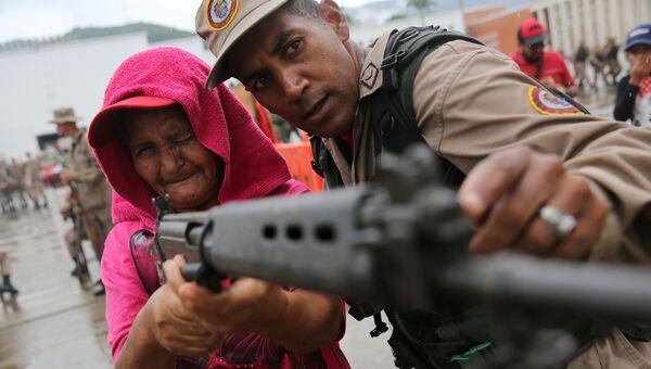 Служащий Национальных боливарианских вооруженных сил учит женщину использовать винтовку во время военных учений в Каракасе, Венесуэла
