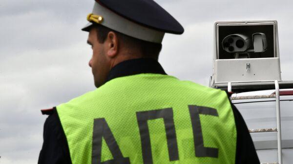 Сотрудник ДПС рядом с мобильным комплексом фотовидеофиксации нарушений дорожного движения