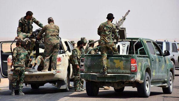 Сирийские военные и бойцы с оружием около города Дейр-эз-Зор, где была прорвана трехлетняя осада ИГ*. Архивное фото