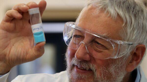 Профессор Грэм Хатчинс держит в руке пробирку с катализатором, позволяющим производить спирт из воздух