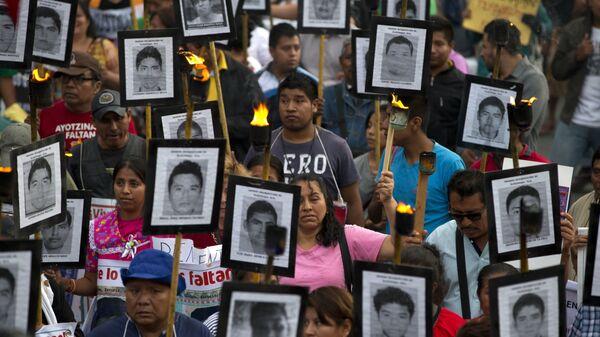 Члены семей и сторонники 43 пропавших студентов несут их фотографии во время марша в Мехико