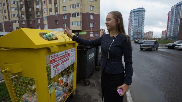 Студентка возле дома в Саранске выбрасывает бутылку в специальный контейнер для пластика.