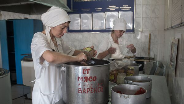 Заключенная на кухне готовит мясо. Архивное фото