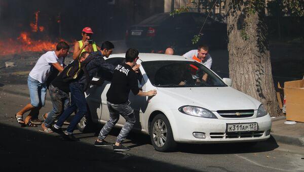 Мужчины отгоняют машину от горящего десятиэтажного здания в центре Ростова-на-Дону