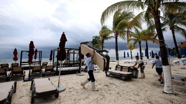 Служащий отеля собирает оборудование в преддверии шторма на побережье Мексики