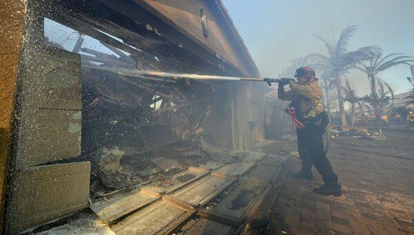 Пожарный тушит дом в Анахайме, Калифорния, США. 9 октября 2017