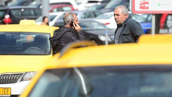 Мужчины разговаривают у автомобилей такси. Архивное фото