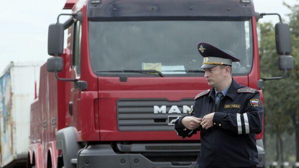 Сотрудник ДПС стоит у брошенного грузовика.