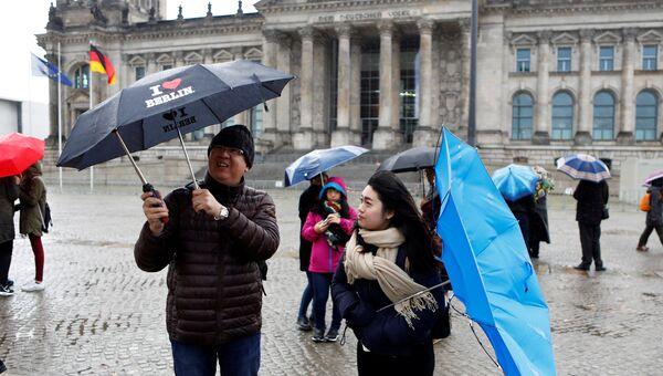 Люди с зонтиками стоят перед Рейхстаг в Берлине, Германия. 29 октября 2017 года