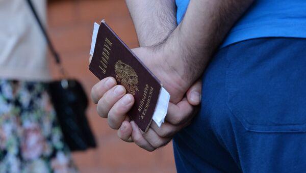 Мужчина с паспортом гражданина РФ в руках. Архивное фото