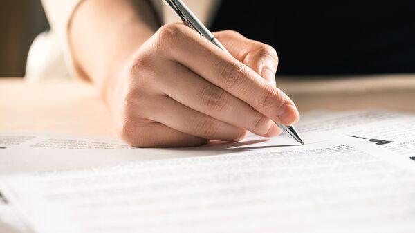 Мужчина подписывает документы. Архивное фото