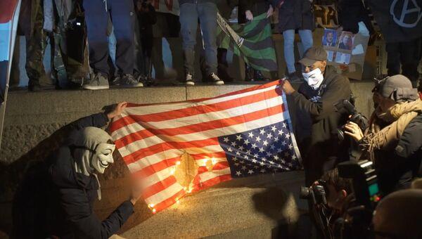 Активисты Anonymous сожгли флаг США на Марше миллиона масок в Лондоне