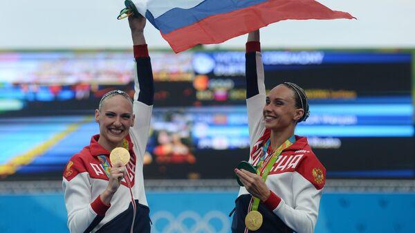 Светлана Ромашина и Наталья Ищенко (Россия), завоевавшие золотые медали на соревнованиях по синхронному плаванию среди дуэтов на XXXI летних Олимпийских играх, во время церемонии награждения. 2016 год