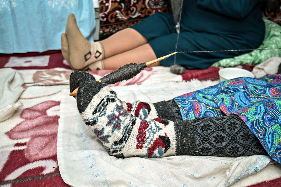 Для удобства по привычке Шагидэ эби держит веретено ногами. На ногах обязательно теплые носки, связанные своими руками