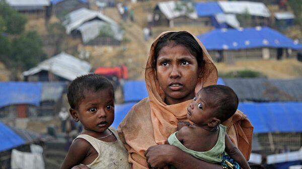 Женщина с детьми в поисках места для жилья в лагере Балухали на границе Мьянмы и Бангладеш