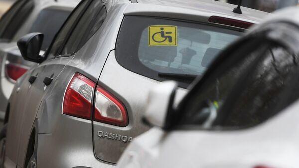 Опознавательный знак Инвалид под стеклом автомобиля