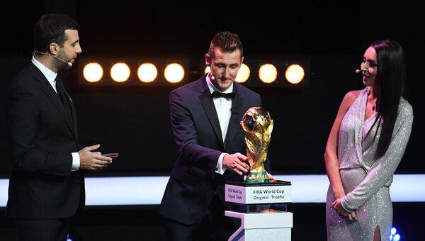 Ведущий церемонии шоумен и актер Иван Ургант, немецкий футболист Мирослав Клозе, певица Алсу (слева направо) с кубком чемпионата на официальной жеребьевке чемпионата мира по футболу 2018