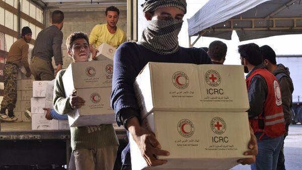 Сирийцы разгружают грузовик с гуманитарной помощью от МККК и Сирийского арабского Красного Полумесяца