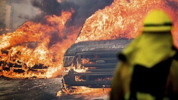 Автомобили, охваченные пламенем от лесного пожара, в городе Вентура в Калифорнии, США