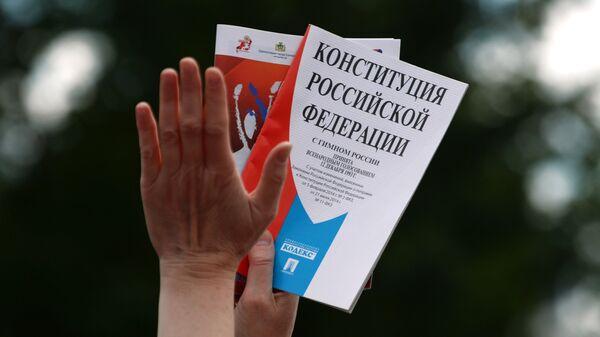 Участник празднования Дня России с Конституцией в руках