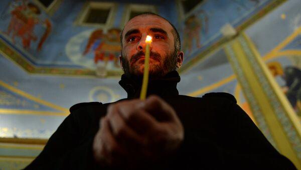 Верующий во время пасхальной службы в церкви Михаила Архангела в Грозном
