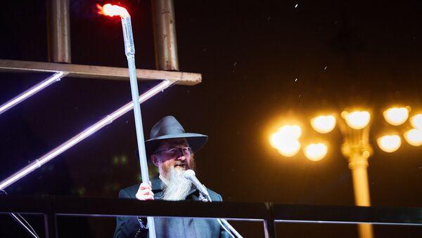 Главный раввин России Берл Лазар зажигает ханукальный восьмисвечник на площади Революции в Москве. Архивное фото