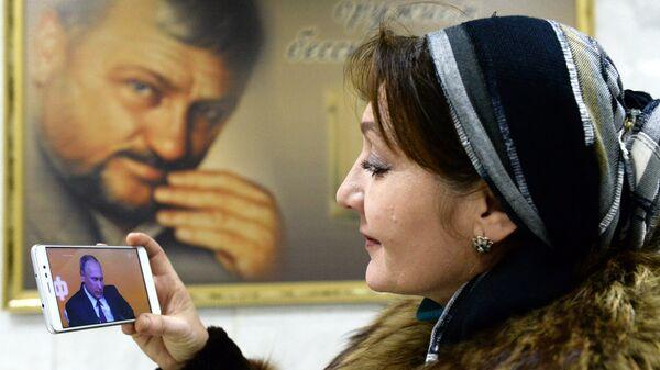Жительница Грозного смотрит трансляцию пресс-конференции президента РФ Владимира Путина