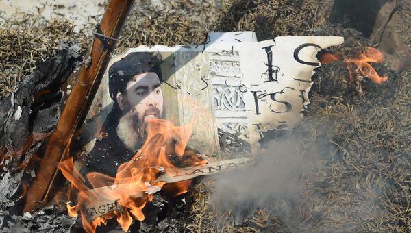 Портерт лидера Исламского государства* Абу Бакра аль-Багдади сжигают во время демонстрации в Индии. Архивное фото