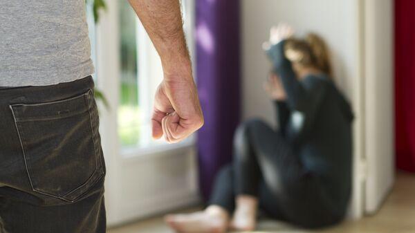 Женщина защищается от ударов мужчины.