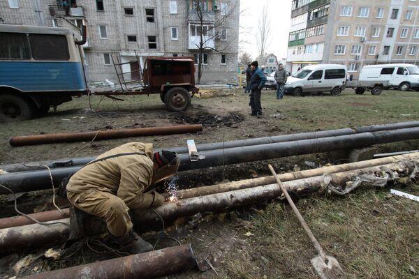 Сотрудник ЖКХ ремонтирует трубы жилого дома в городе Ясиноватая, пострадавшего в результате обстрела. 21 декабря 2017