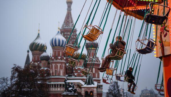 Дети катаются на карусели на Красной площади в Москве