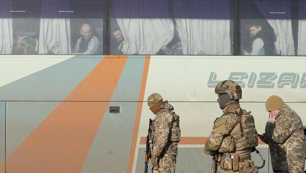 Украинские военные рядом с автобусом, перевозящим военнопленных ДНР и ЛНР к месту обмена