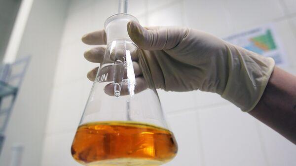 Сотрудница в лаборатории контроля качества на заводе по производству жидких противогололедных материалов