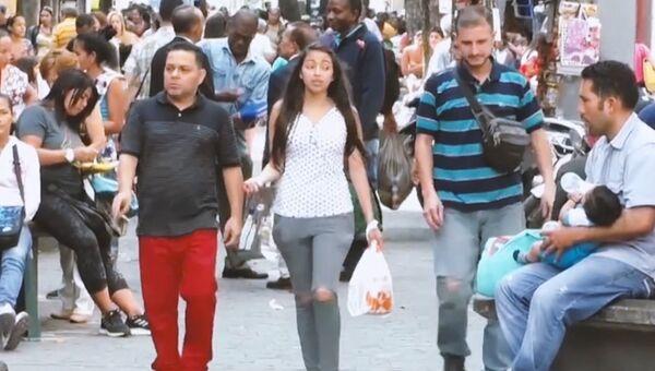 Прохожие на улице в Каракасе. Архивное фото