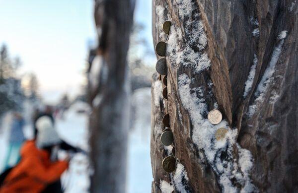 Китайские туристы оставляют монетки у деревянных идолов в саамской деревне Самь-Сыйт в поселке Ловозеро Мурманской области