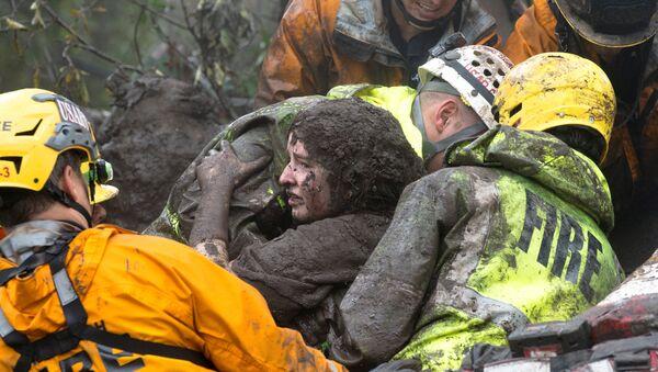 Сотрудники спасательных служб несут женщину, спасенную из дома, рухнувшего после оползня в Монтесито, штат Калифорния, США. 9 января 2018