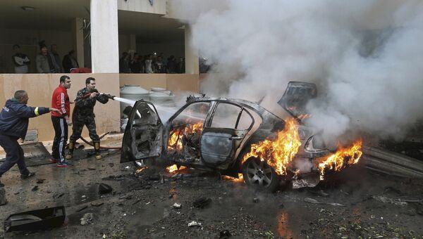 Пожарные тушат автомобиль поврежденный взрывом в городе Сайда, Ливан. 14 января 2018