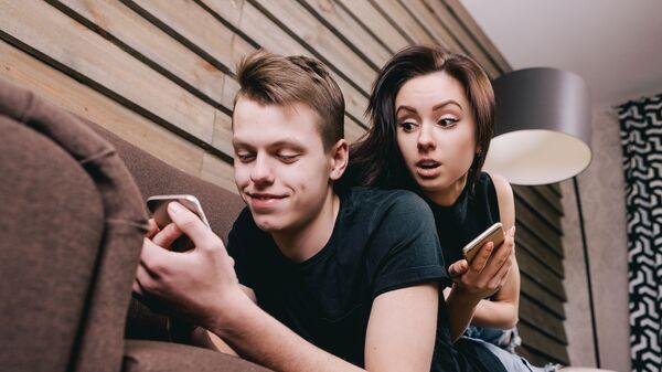 Молодая пара с мобильными устройствами