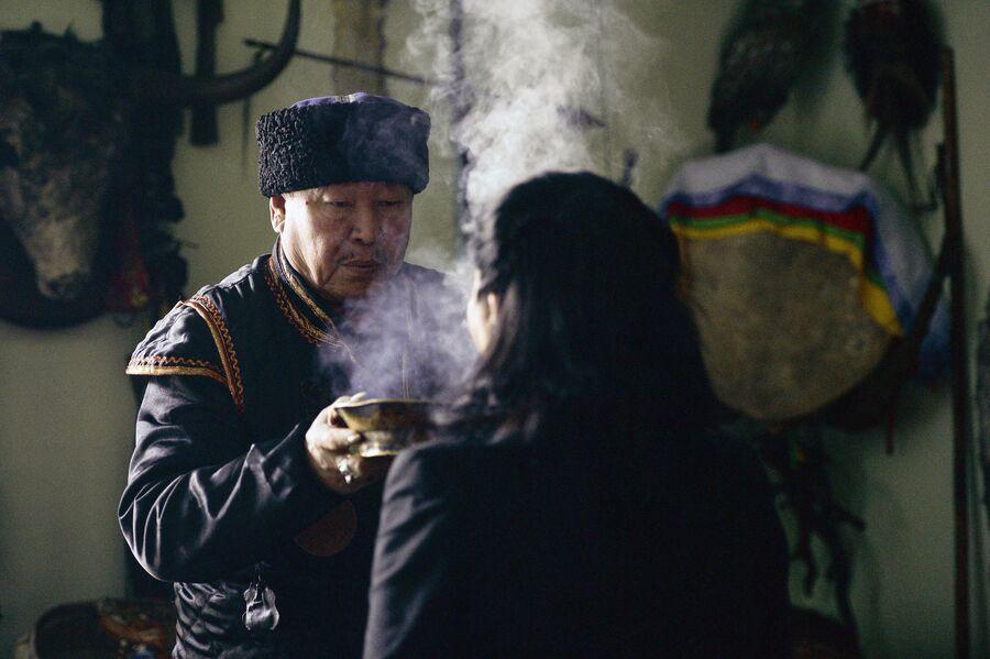 Председатель шаманского общества Адыг-Ээрен (Дух медведя), верховный шаман Республики Тыва Кара-оол Тюлюшевич Допчун-оол проводит обряд с посетителем в своей комнате в доме, который занимает шаманское общество в Кызыле