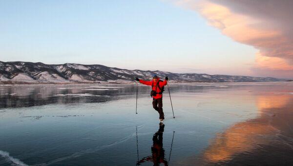 Мужчина на коньках на льду озера Байкал