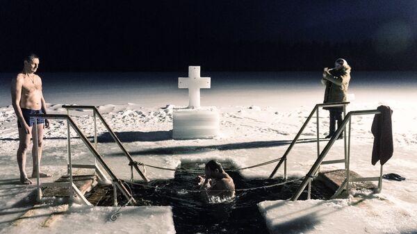 Верующие во время традиционного праздничного купания в Крещенский сочельник на территории Валдайского Иверского Святоозерского Богородицкого мужского монастыря в Новгородской области