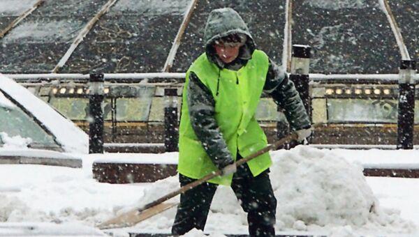 Работник городской коммунальной службы убирает снег на Манежной площади в Москве. Архивное фото
