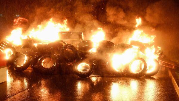 Горящие покрышки во врем акции протеста работников тюрем во Франции