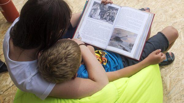 Женщина и ребенок читают книгу