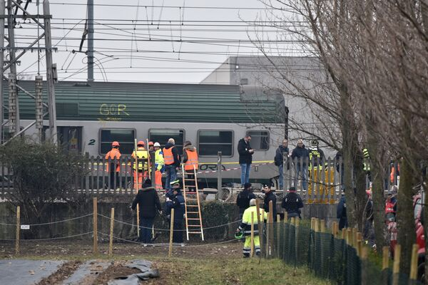 Спасатели и полицейские на месте крушения поезда на окраине Милана, Италия. 25 января 2018 года