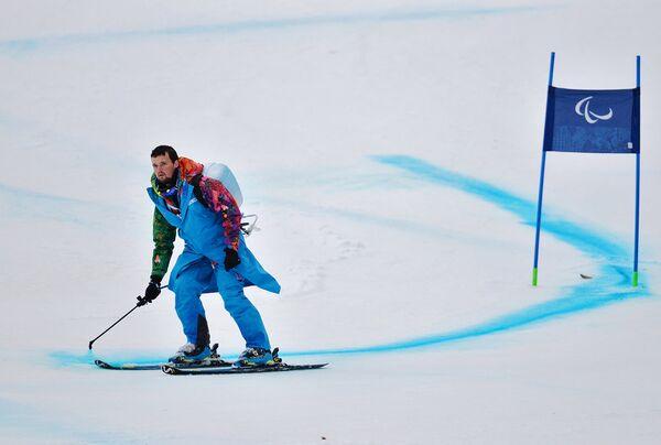 Волонтер обновляет разметку трассы на соревнованиях по горнолыжному спорту среди женщин на зимних Паралимпийских играх в Сочи