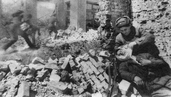 Сталинград. Декабрь 1942 г. Уличный бой. Санитарка перевязывает раненого. Архивное фото