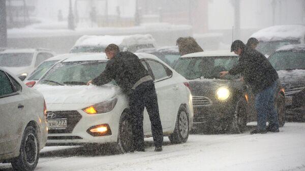 Владельцы отчищают свои машины от налипшего снега во время снегопада. Архивное фото